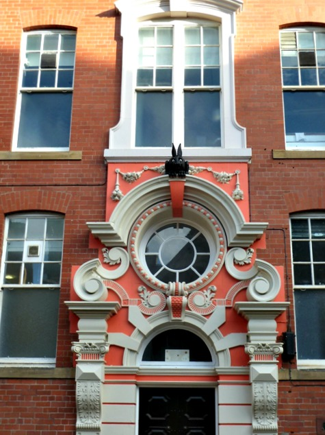 The ornate pink and white stone work over the top of the back door of the cathedral buildings in Newcastle