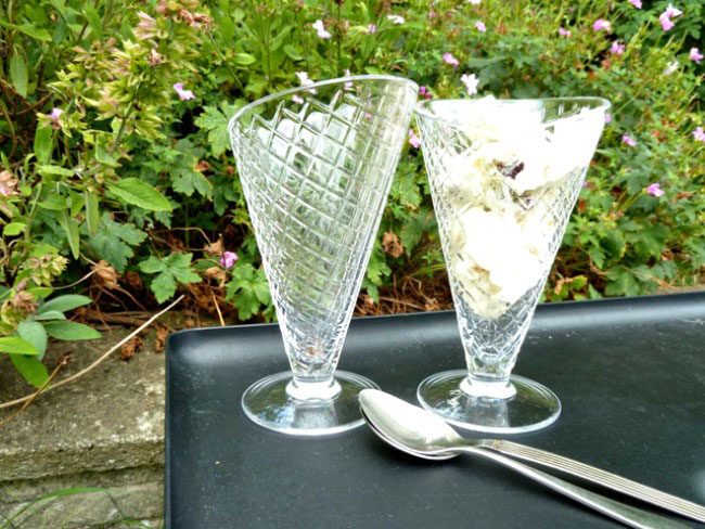 Tutti frutti ice cream served in a sundae dish on a table outside with spoons