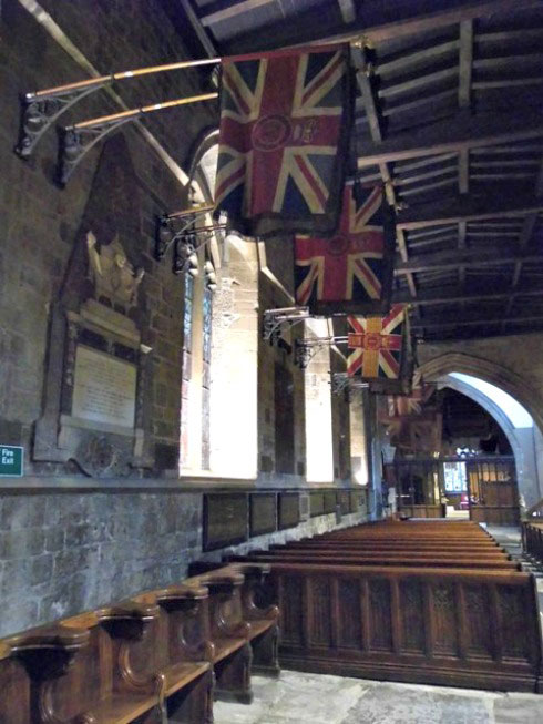 Regimental flags hanging from the wall of Newcastle cathedral
