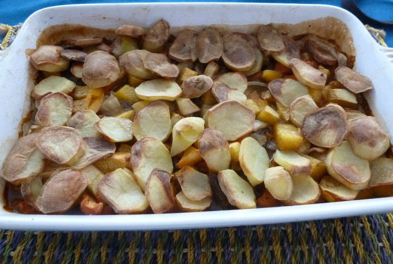 Panaculty, a dish of left over meats stock and root vegetables topped with sliced potatoes in a casserole dish on a table mat