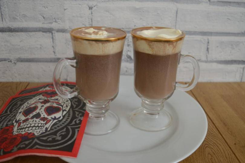 two glasses of Mexican hot chocolate with cream on top on a plate