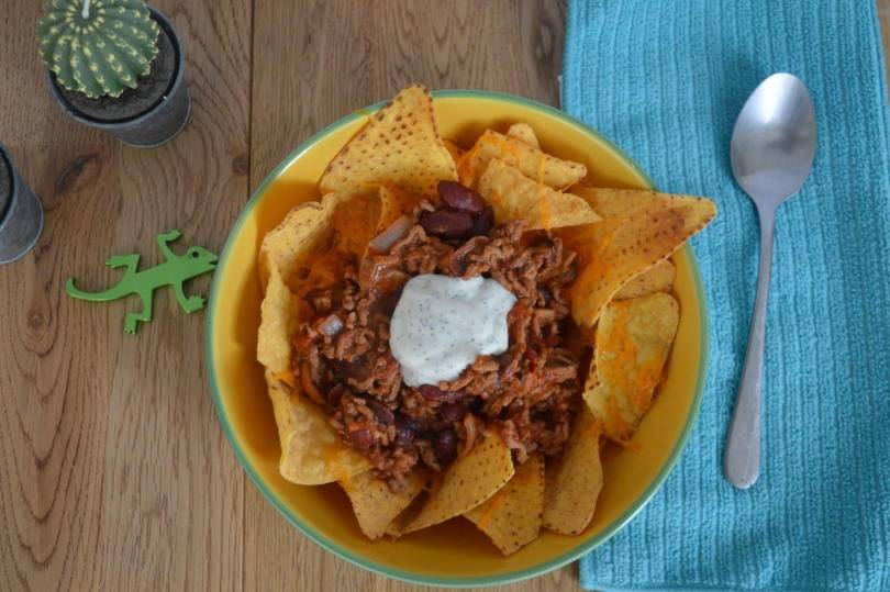 Simple beef nachos on a plate with sour cream on top