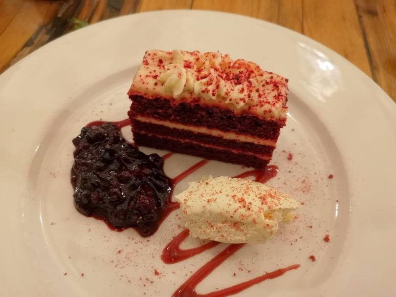 Red velvet torte on a plate with red berry compote and cream