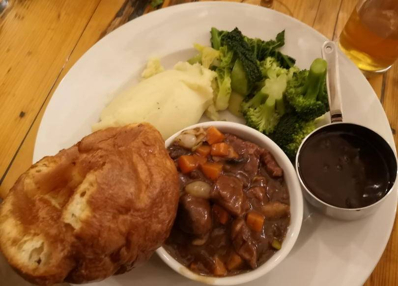 steak and mushroom casserole on a plate with mash, gravy in a little bowl and a yorkshire pudding