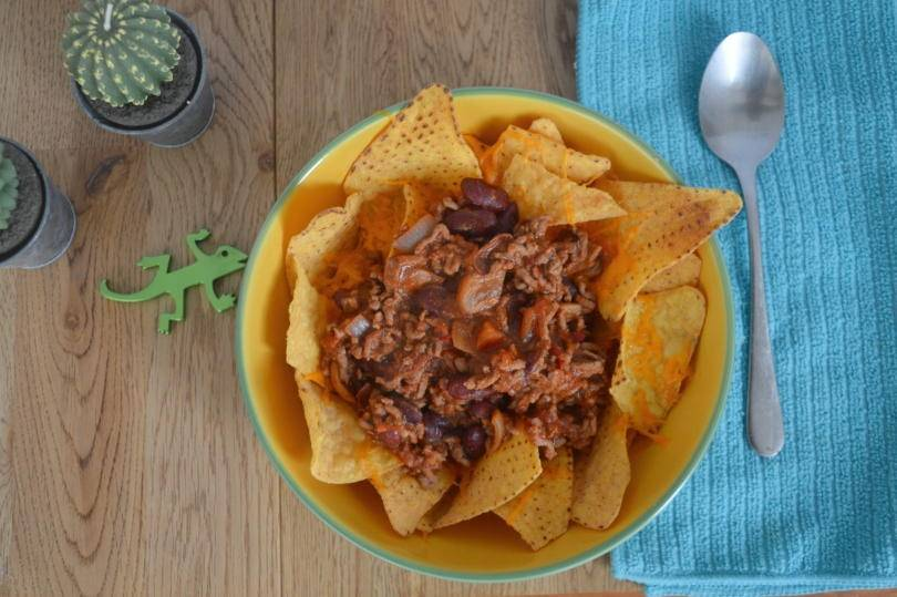 beef topping tortilla chips in a bowl on a table