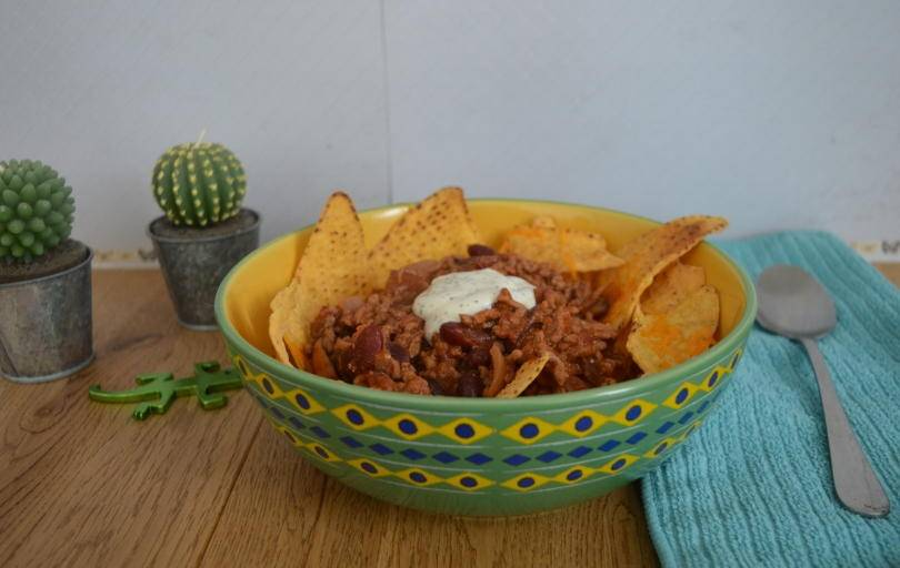 beef topping tortilla chips in a bowl with sour cream on top.