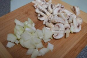 chopped onions and mushrooms on a chopping board