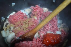 Mince onions, mushrooms, chilli and cunin in a pan
