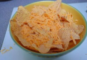 Tortilla chips in a bowl with cheese grated on top
