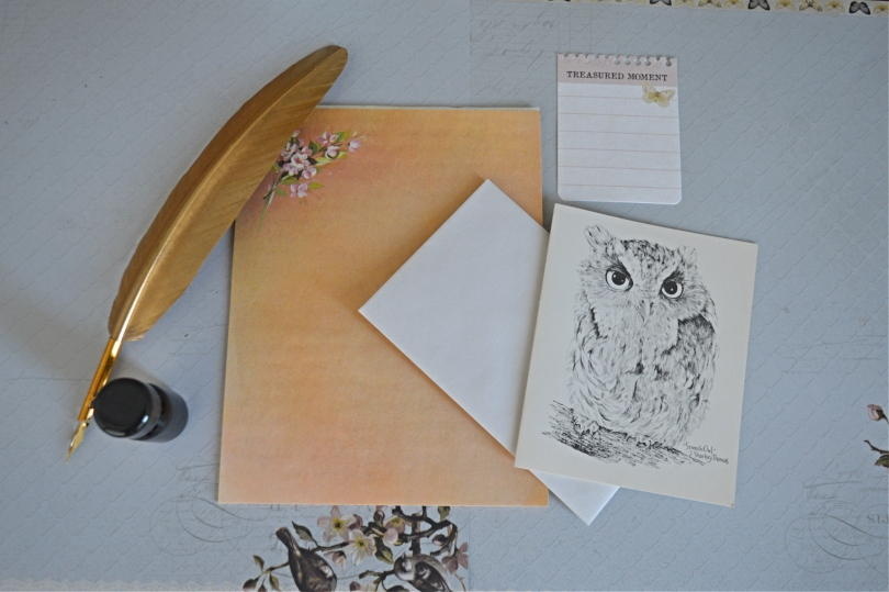 Gold quill pen and ink with orange notepaper and owl notelet on a grey background