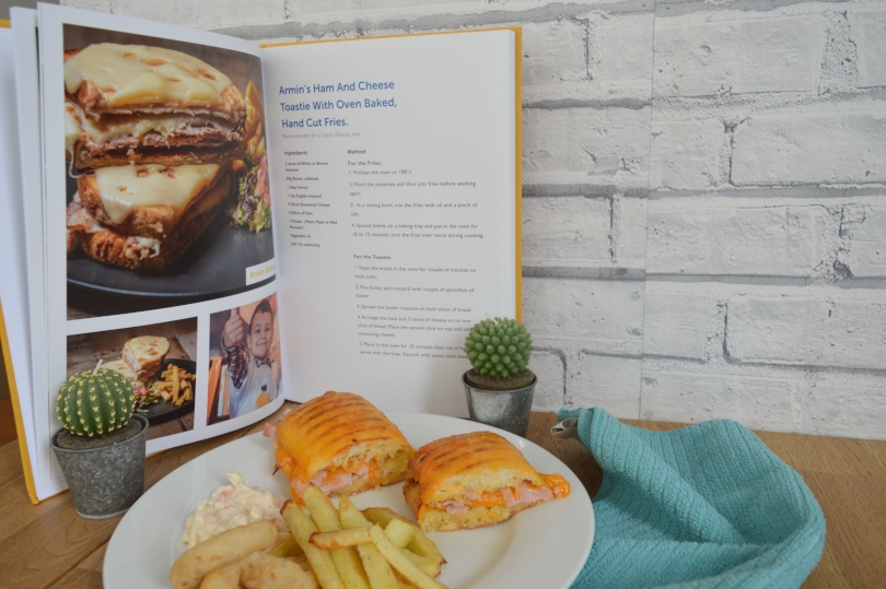 Ham and cheese toastie on a plate with a picture from the cookbook behind