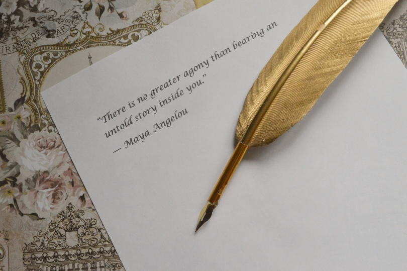 """Quote """" There is no greater agony than bearing an untold story inside you"""" on paper with gold quill pen beside it"""