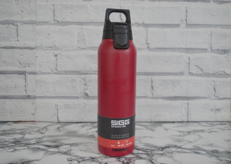 Sigg hot and cold one water bottle. It is a red colour and on a table with a wall behind