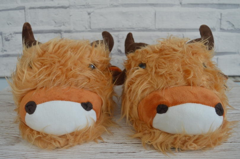 A pair of slippers that look like Highland cows
