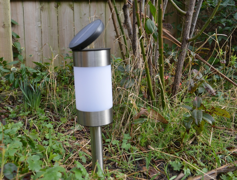 A stake solar light with the panel tilted to catch the light in the garden