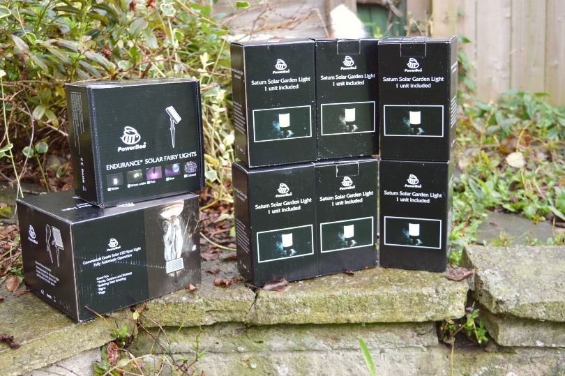A selection of different types of solar lighting from PowerBee in boxes on a wall