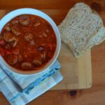 sausage and bean soup in a bowl on a table with a slice of bread beside it