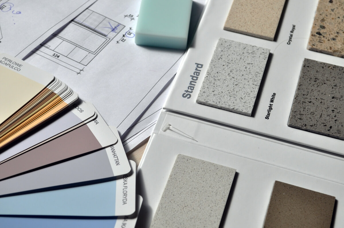 Table with paint swatches and tile samples laid out on it.